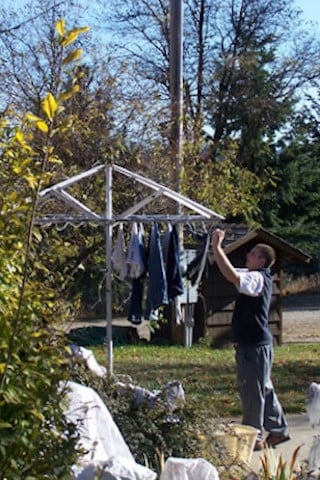 Alec hangs the men's laundry out in the brisk fall  sunshine. All the retreatants sign up on the chore  rota for the month long retreat.