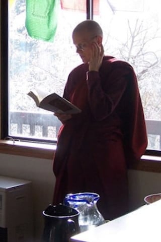 Venerable Tarpa stands next to a window and reads from a Dharma book