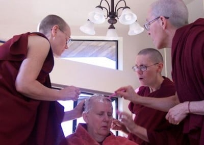 Three nuns encircle Dianne as they shave her head