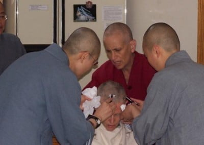 Jan gets her head shaved by the bhikshunis to represent her letting go of attachment.