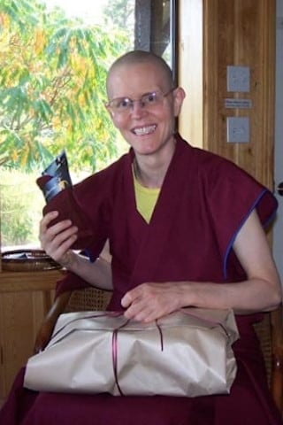 The day after, Venerable Thubten Tarpa relaxes and shares a happy moment opening some of the lovely and practical gifts she received from her Dharma friends.