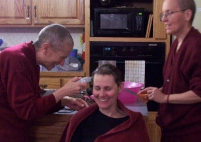 Venerables Chodron and Semkye begin the hair cutting to make the head shaving easier.