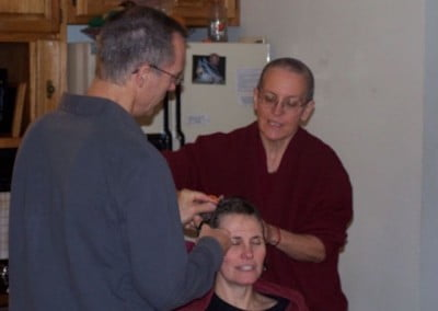 Venerable Semkye and another person shave Barbara's head