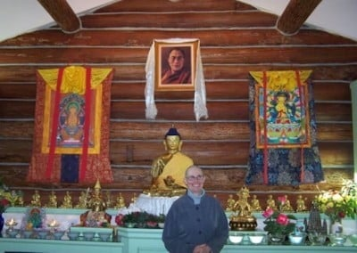 Barbara stands in front of the altar in the meditation hall for a quick photo