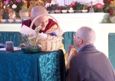 Barbara bows and kneels at Venerable Chodron's side as she makes an offering
