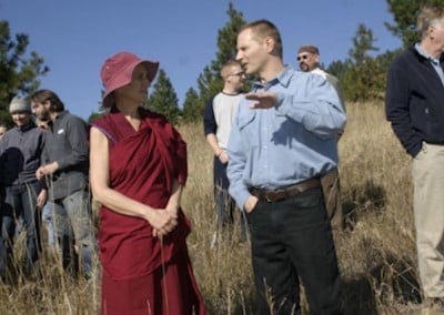 Tim Wilson shares some thoughts with Venerable Chodron as he looks over <br> the site of the proposed building. Green materials and the use of the terrain will play an important part in the construction of the residence.