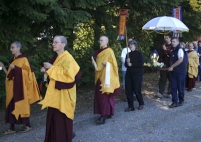 The sangha follow the conches with bells and incense honoring the Buddha.