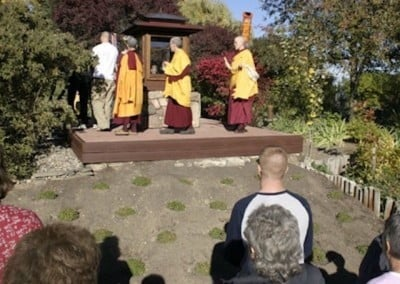 Residents circumambulate the Buddha statue in the garden while guests watch