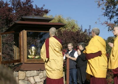 As we chant the Buddha's mantra, the Buddha is placed in the house and the protective glass door is closed.