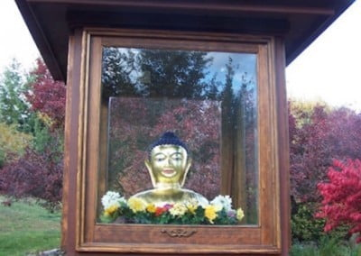Bust of the Buddha in its wood housing in the garden