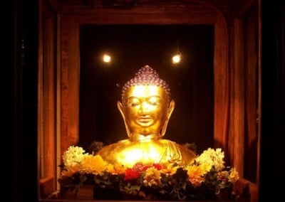 The Buddha appears to emanate replicas of himself in the glass windows of his new home.