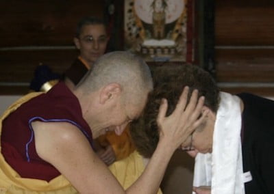 Venerable Chodron holds the head of a student in both hands as they bow to each other