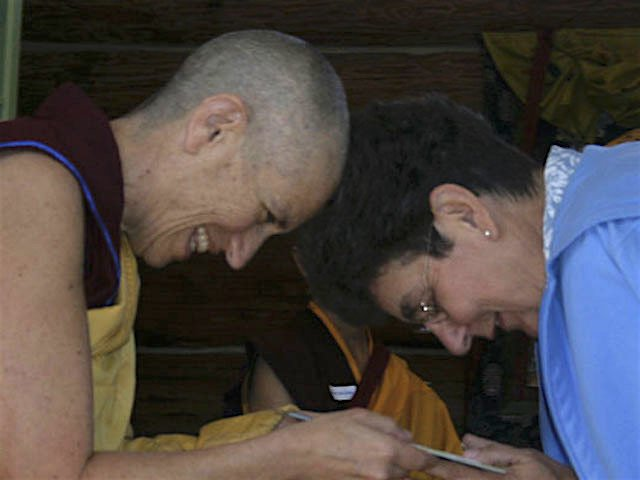 Jo Simpson and Venerable Chodron bow to each other as Venerable offers Jo a gift