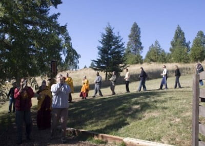 Single file the sangha leads the guests down the path into the backyard.