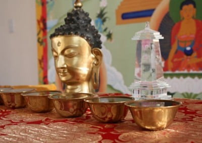 Closeup of the alter with the Buddha, water bowls and a crystal stupa