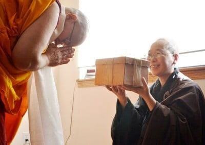 Venerable Yeshe offers Venerable Jendy a gift for her wisdom and encouragement.