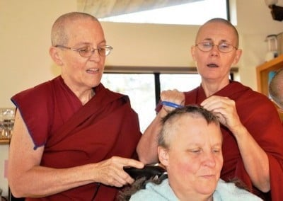 Venerables Semkye and Chonyi chant the Buddha's name while shaving Terri's head.