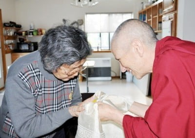 Venerable Mingjia's mother, Lao Pusa, accepts a gift from the abbess.