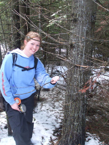 Student Becky Hamm poses near an example of a resin flow caused by the fungus Armellaria. This is the tree's way of trying to fight the disease.