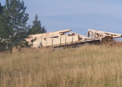 A semi full of wood trusses drives down the fire road to the construction site