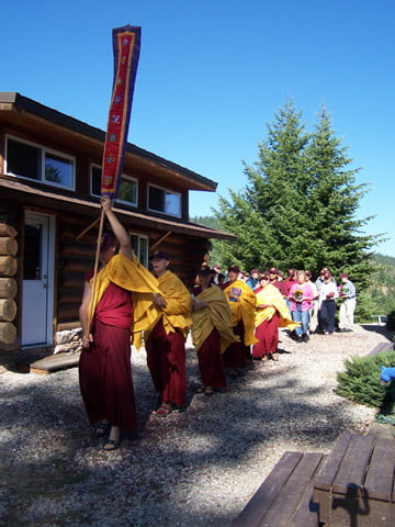 Monastics and guests follow a procession past the meditation hall