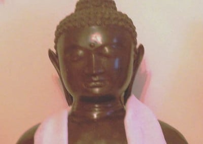Closeup of the bust of the Buddha with a khata
