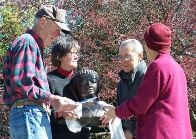 Barbara holds the bust of the Buddha while Venerable Chodron and 2 guests stand around her in the garden