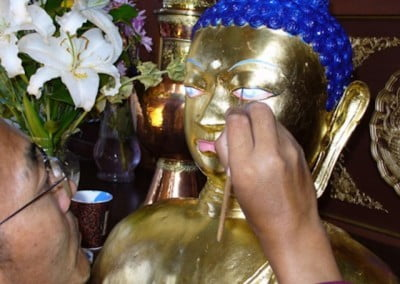 Someone painting the eyes of the Buddha bust