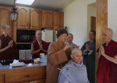 Nanc gets her head shaved by the bhikshunis first thing in the morning as guests chant the Buddha's mantra.