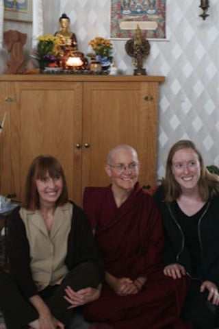 Venerable Semkye poses for a photo with her sister and niece on the floor in front of the altar in Ananda Hall