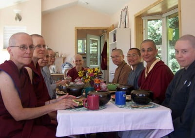 Nine monastics sit at the dining room table eating