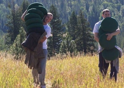 Two men carry large stacks of meditation cushions through the meadow