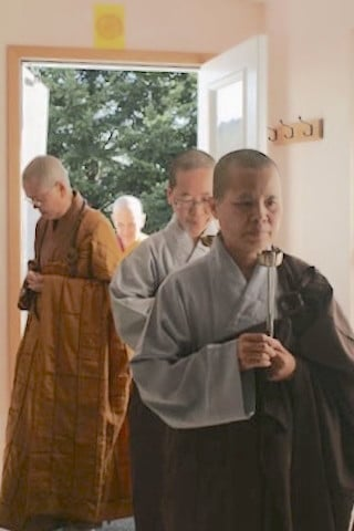 Bhikshunis Jencheng, Jendy, Mingjia and  Chodron enter the meditation hall before the start of the ceremony.