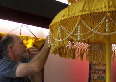 Dwight, one of the local volunteers helps put the finishing touches on the parasol.