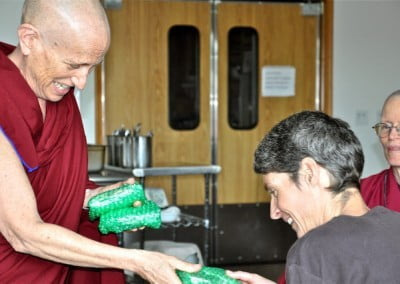 Ven. Chodron offers a beautiful Lama Tsong Khapa tsa-tsa to Peggy.