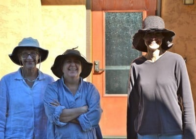 Three women in floppy hats, smiling and standing in the sun