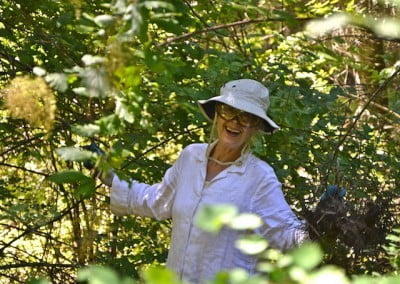 Woman in white hat in the forest, smiling