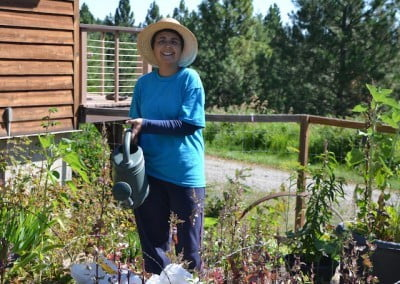 Woman in blue smiling and watering garden plants