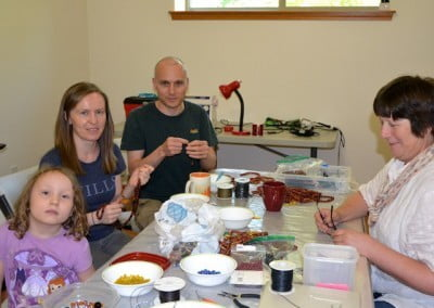 Meery, with her parents Brielle and Keith,  helps Tracy string malas for the incarcerated.