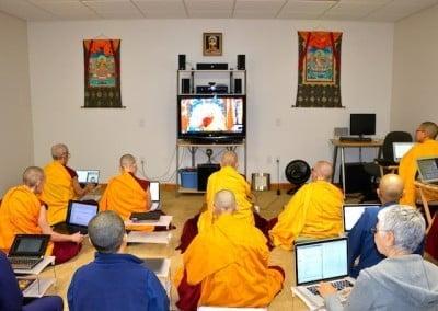 Buddhist nuns and lay people watching Buddhist teacher on TV monitor