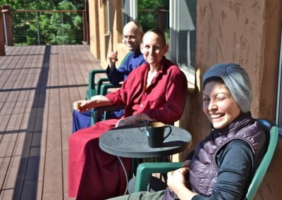 Buddhist nun and lay people sitting outside on a verranda