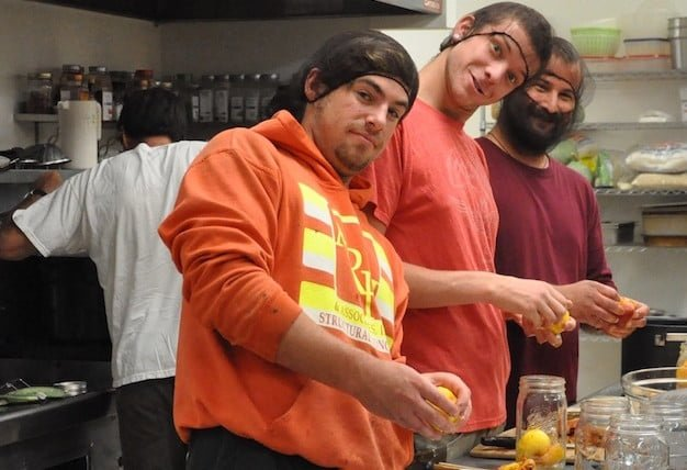 A volunteer crew learns to can peaches.