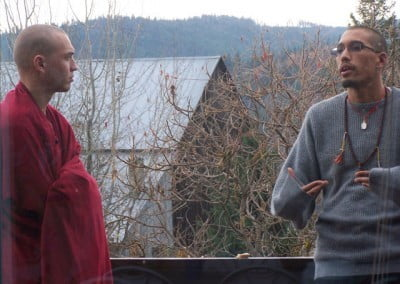 Monk and layman talking on a deck in fall