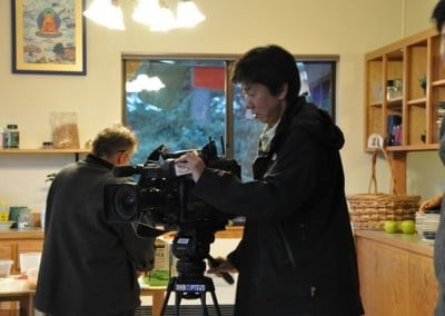A Korean film crew from a Buddhist TV station is doing a documentary on Buddhism in the West. They stopped by Sravasti Abbey one day and spent the day filming a number of activities. Here they are preparing to film the Bodhisattva Breakfast Corner, Venerable Chodron's morning motivational talk that is posted daily on YouTube.