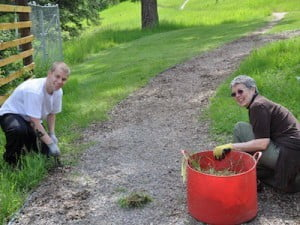 Young and & older woman trim the grass.