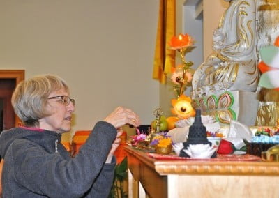 Julie helps set up the altar for the Lama Chopa Puja.