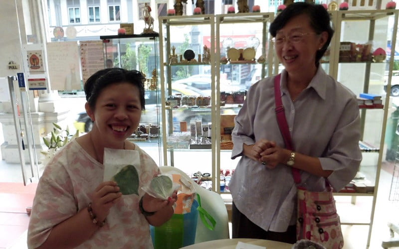Mom and grown daughter in shop showing ceramic bodhi leaves.
