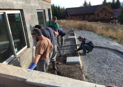 Workers pour the cement patio.