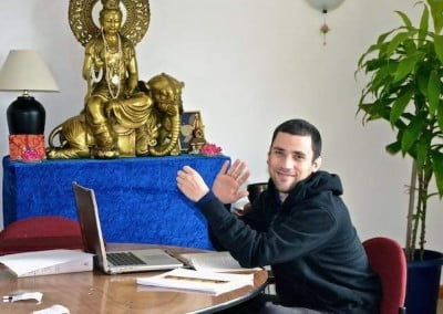 smiling man sitting at table with Buddhist statue