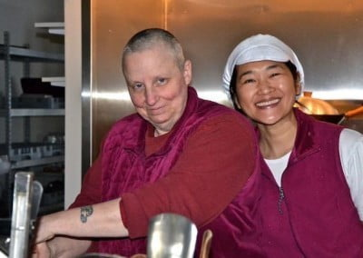 smiling nun and lay woman cooking